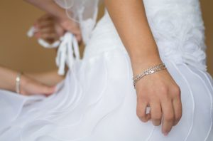 Bride Waiting Patiently while Her Assistant Adjusts Wedding Dress